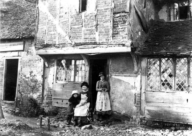 Straw plaiters at the door of their cottage. Next door was a beer-house, whose landlord's name, Frederick Balls, can be seen on the sign above the door. The cottages were demolished about 1910 and a new pub, The Hermit of Redcoats, was built.