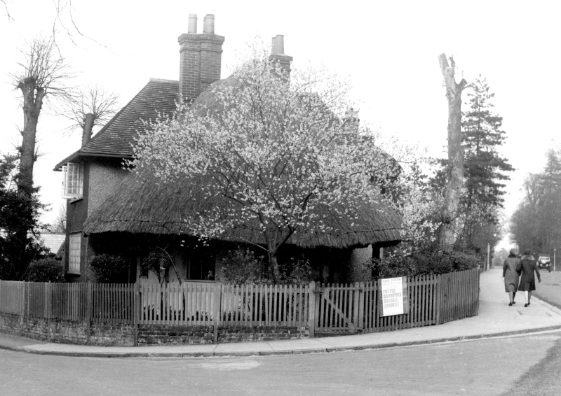 A view of the house at the junction of Walsworth Road and Whinbush Road, with its rounded south wing. Its thatched roof was later replaced with wooden shingles. The candidates for an Urban District Council election in 1930 are named on the poster.