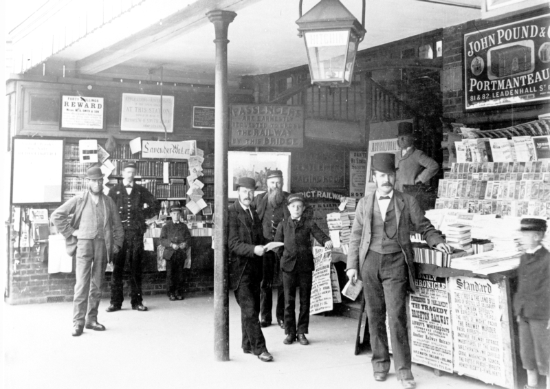 Hitchin Station, July 1881.Staff and customers on the platform at Hitchin Railway Station pose for the camera. On the right is the bookstall, with its assistant, John Sydney Pink (1856-1934) from Cambridge, standing beside it. The boy in the cap on the right may be another employee. Jack Webb (1850-1906), a cab driver and the licensee of The Cooper's Arms, stands on the stairs to the footbridge, behind. The footbridge was known as the Hitchin Alps owing to the steepness of its stairs; it was removed in 1910. The bearded man in uniform in the background towards the centre is Inspector Henry Charles Fisher (1831-1909). The porter, second from left, is Edward (Teddy) Hayward (1852-1913), who lodged nearby in Midland Cottages.