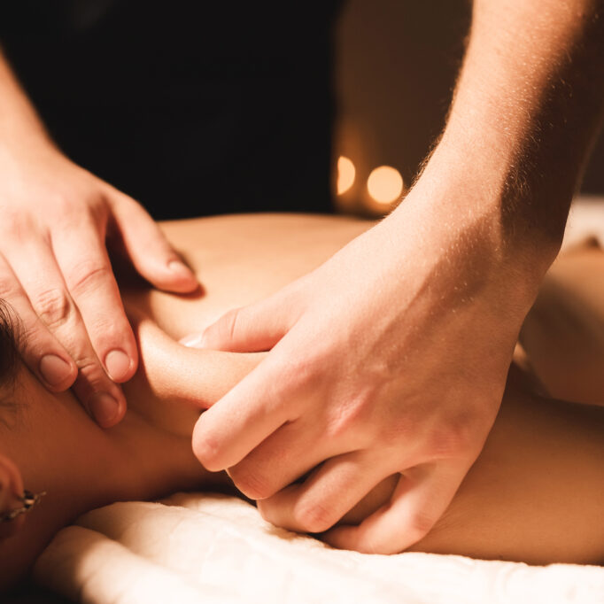 Men's hands make a therapeutic neck massage for a girl lying on a massage couch in a massage spa with dark lighting. Close-up. Dark Key.