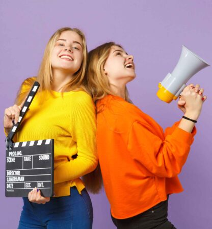 Two teenage girl acting students one holding a clapper board and the other holding a mega phone