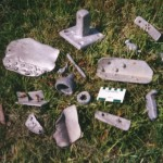 Assorted smaller aluminium wreckage including a door knob. There is also a square plate of 13.2cm side with attached square post 4cm long. The base plate retains a single rusty iron screw 6cm long. Scale in cm and inches.