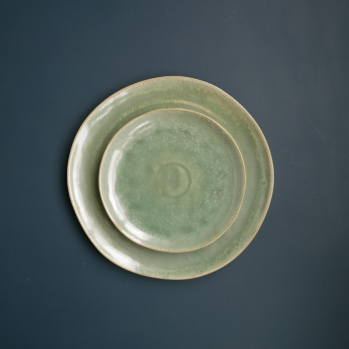 green-glazed-plate-&-side-plate-stacked-blue-background