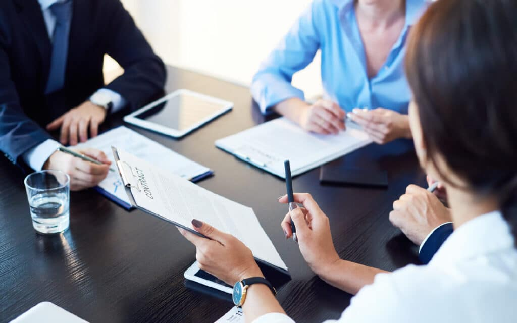 Image of small team with iPad and documents around a desk