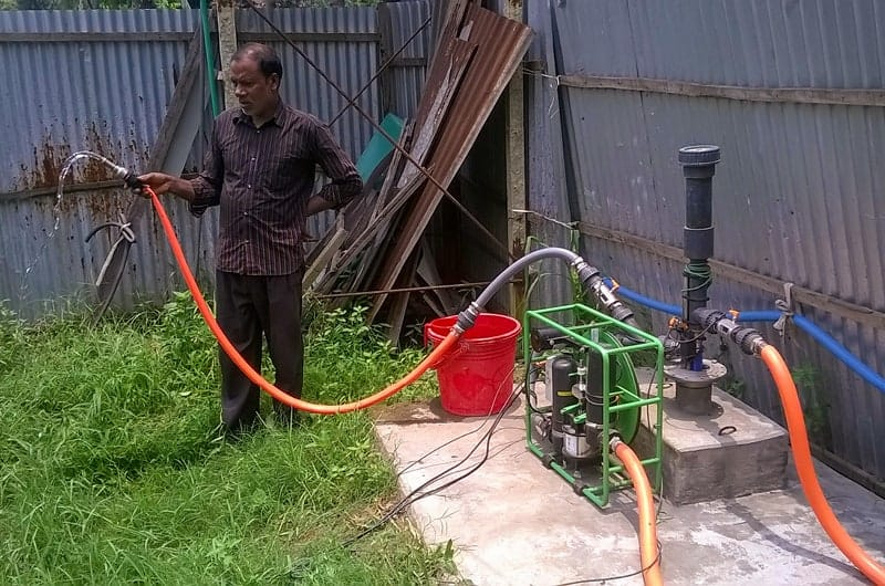 An Impact Pump field trial set up in Bangladesh with a farm worker spraying water.