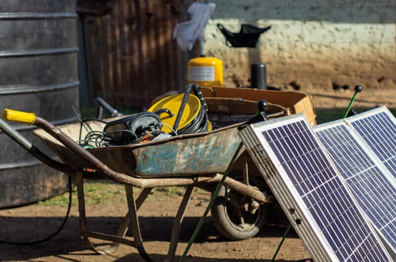 Wheelbarrow and solar panels near an Impact Pump installation