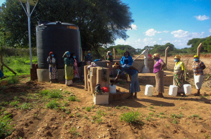 A queue of women wait at a water point in front of a water tank and solar panel set up