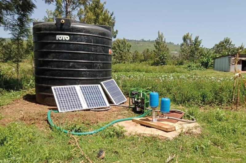 The Impact Pump, a submersible hydraulic ram pump, set up on a farm next to a tank and powered by the Futurepump SF2 a solar powered surface pump