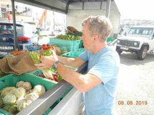 Carl gathering produce on tiptoe