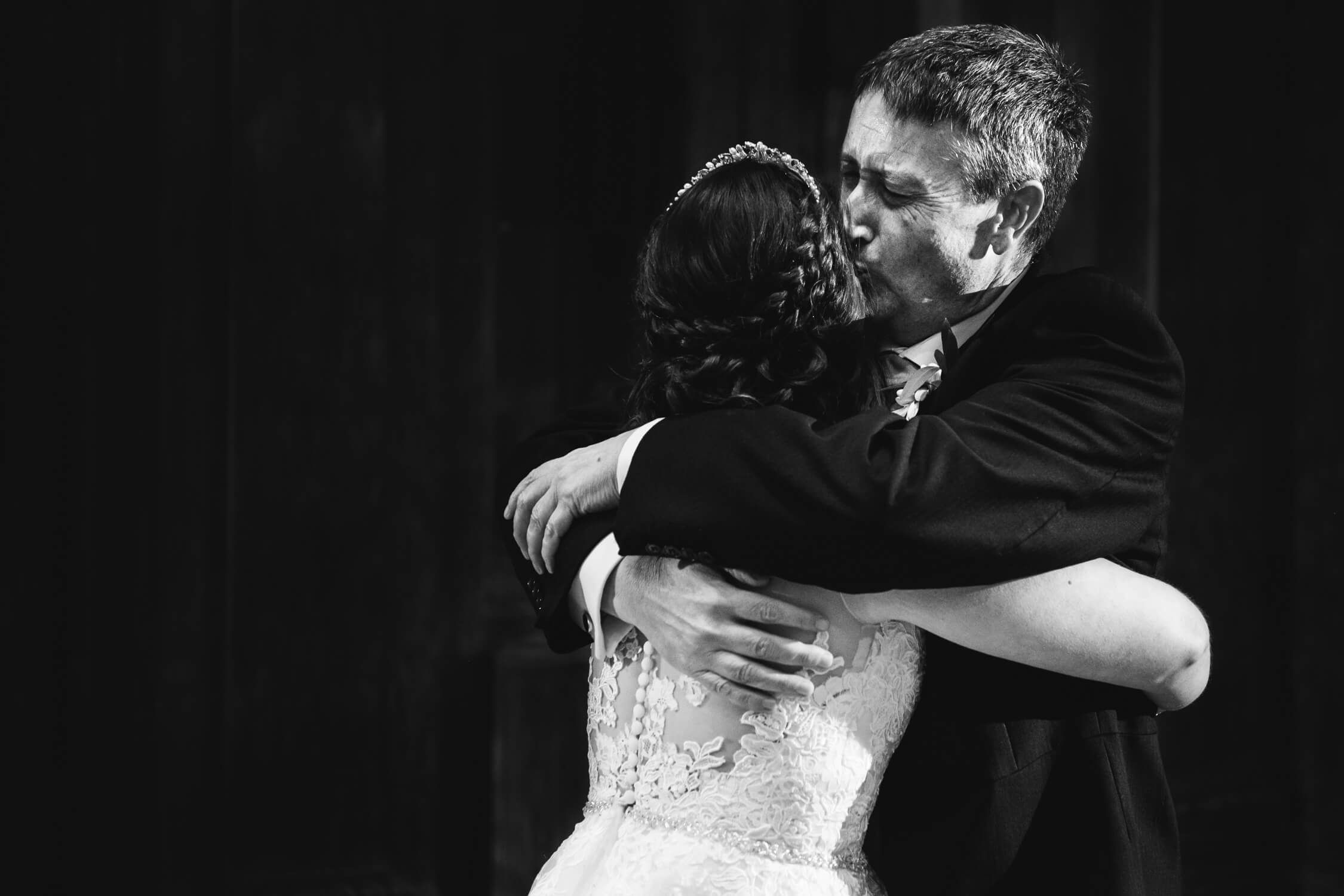 Father of bride kisses daughter after their dance at Fawsley Hall