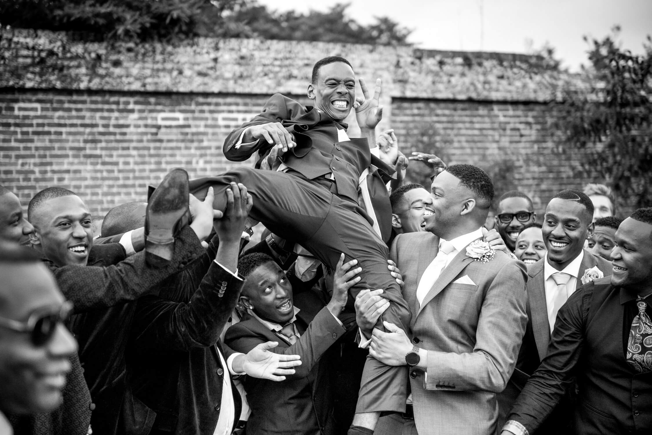 Groom being lifted in the air
