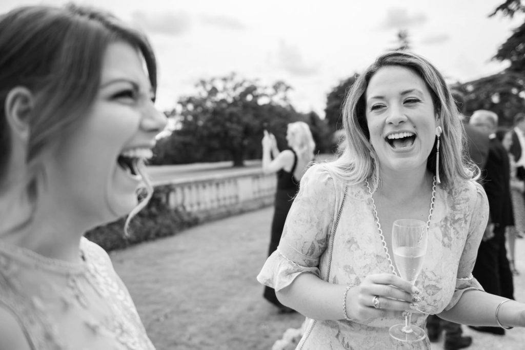 Two wedding guests laughing at Stoke Park