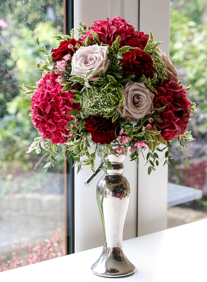 Silver candlestick with Burgundy and blush flowers, created by London florist Garland