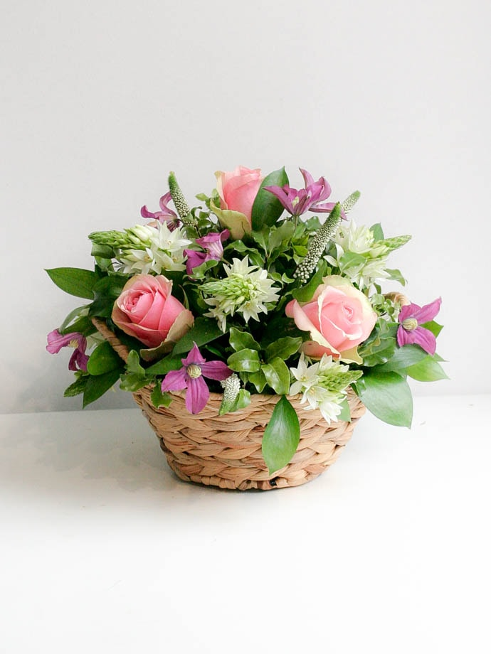 Round basket filled with roses and hyacinth, created by Garland for Mother's Day