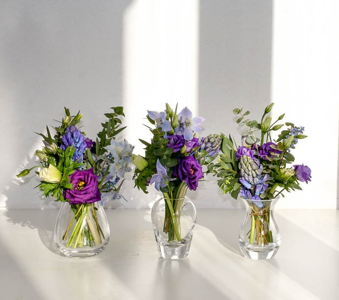 Three bud vases filled with purple and blue flowers, created by Garland London florist