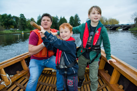 Lagan Currachs team member Tim shows young boys how to steer a currach - photo 9245. Featured image.