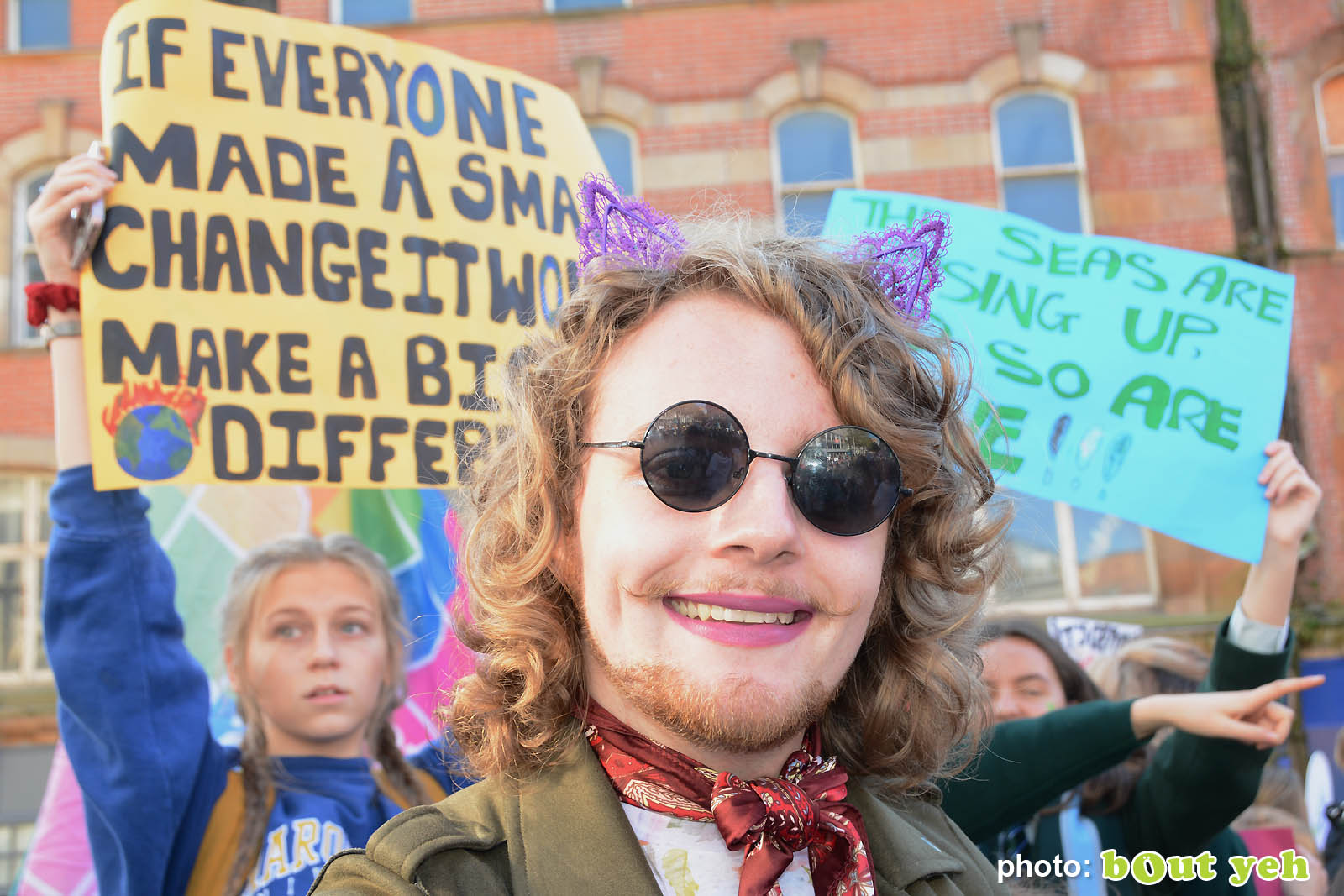 Young man in dark glasses in front of placards at the strike for climate protest in Belfast. Photo 8929 by Bout Yeh photographers Belfast