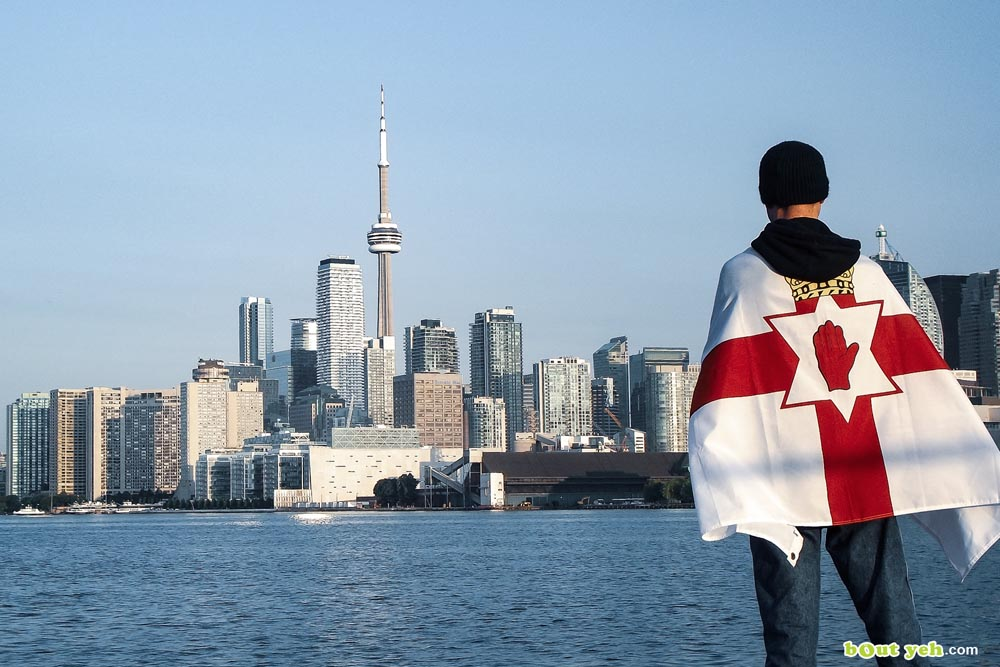 Andrew McLaughlin wearing Ulster flag in front of Toronto Canada - featured photo 4924 shared by Bout Yeh photographers and video production Belfast