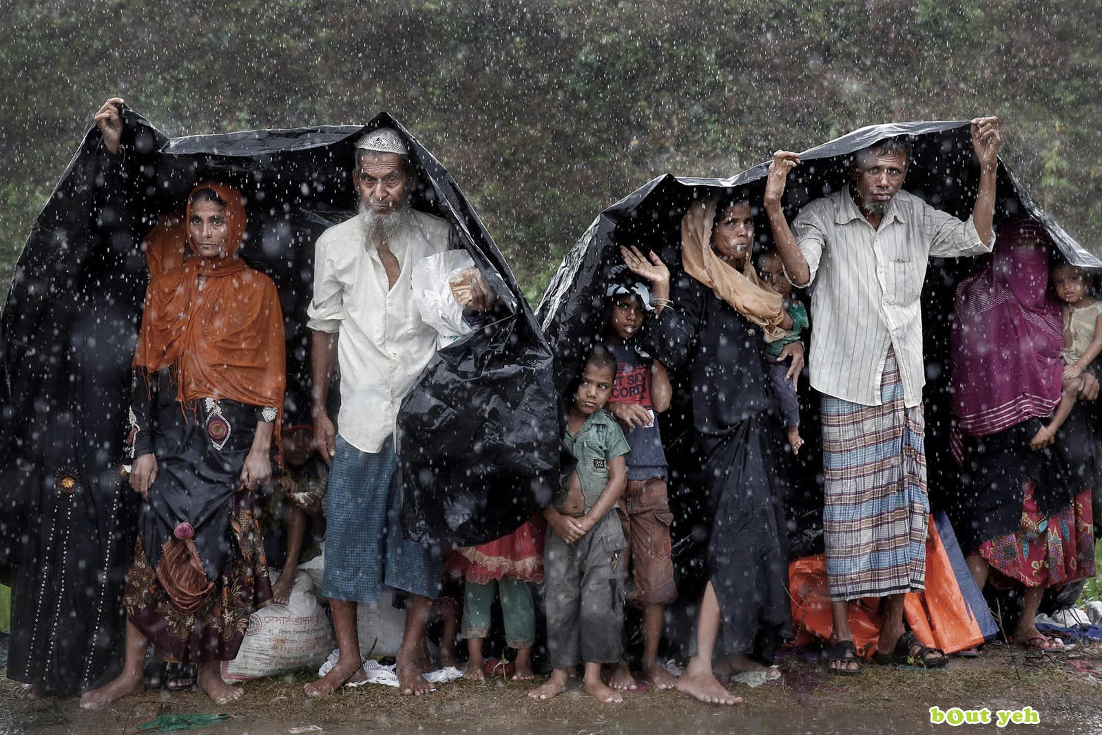 Rohingya refugees shelter from the rain in a camp in Cox's Bazar, Bangladesh - photo by Cathal McNaughton shared by Bout Yeh photographers Belfast