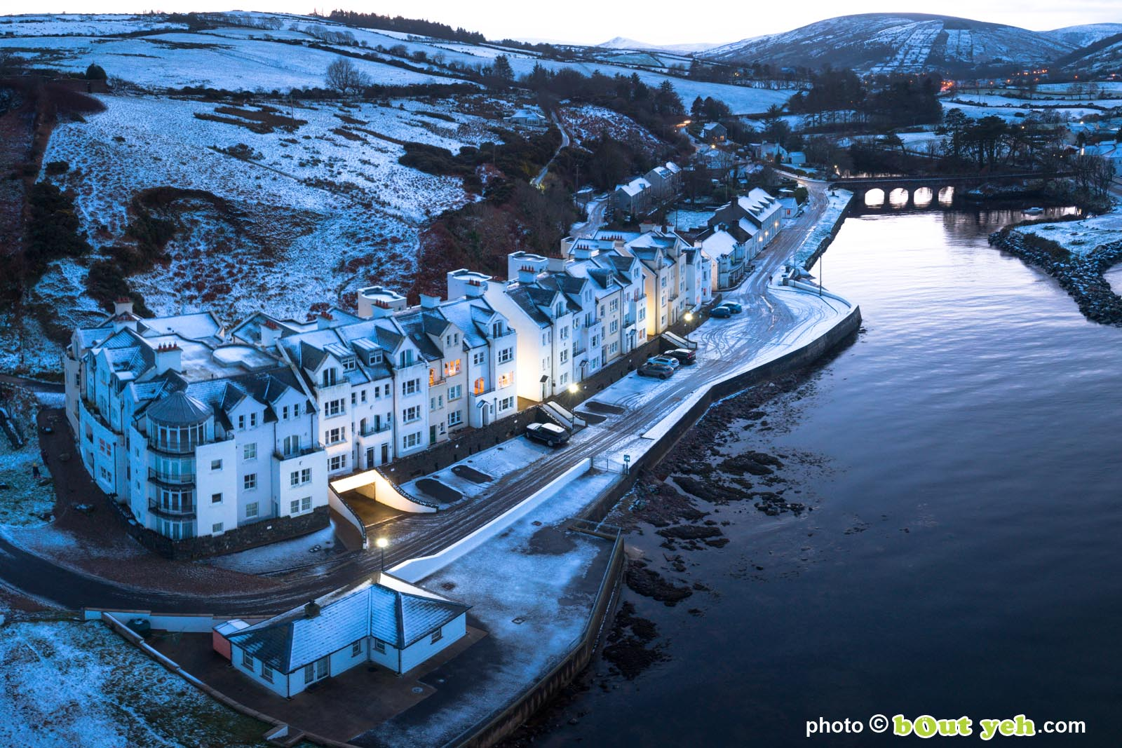 Aerial photograph of Bay Apartments Cushendun, Northern Ireland, in winter under snow at dusk by Bout Yeh photographers Belfast. Photo 231121