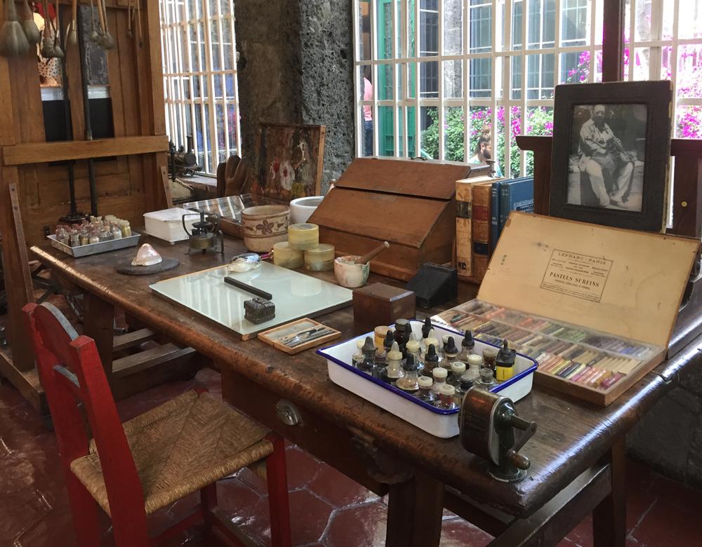 table with paints and materials at frida kalho's studio at casa azul, mexico