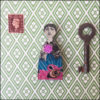fairy brooch pink, blue and black, decoupage on wood next to key and stamp