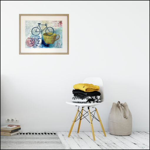 framed giclee print of a bike, a yellow cup and a couple of postal seals on a blue and turquoise painted background, shown on a living room wall