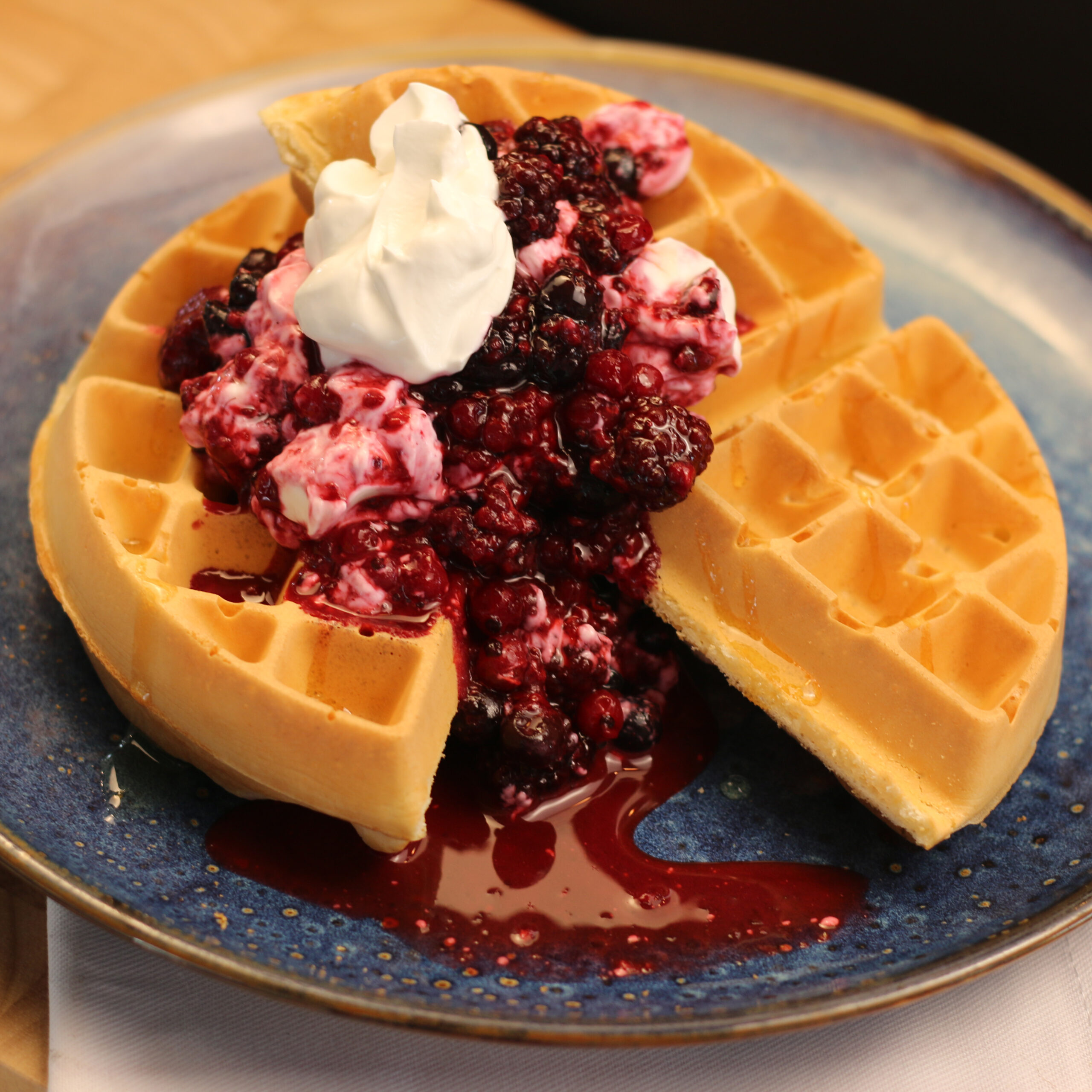 Breakfast berry waffle with yoghurt and honey on a plate