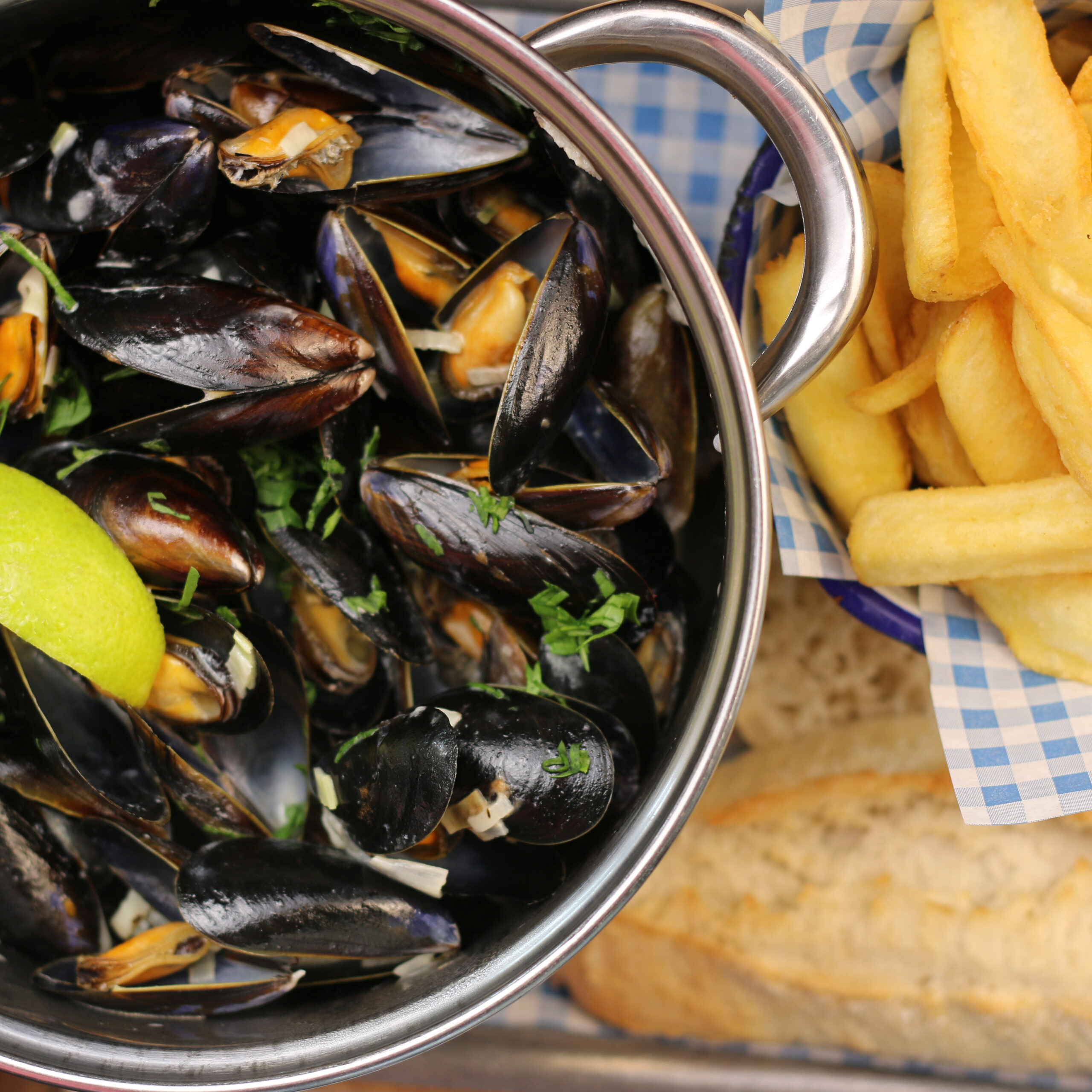 Mussels served in a bowl with a bowl of fries and crusty bread