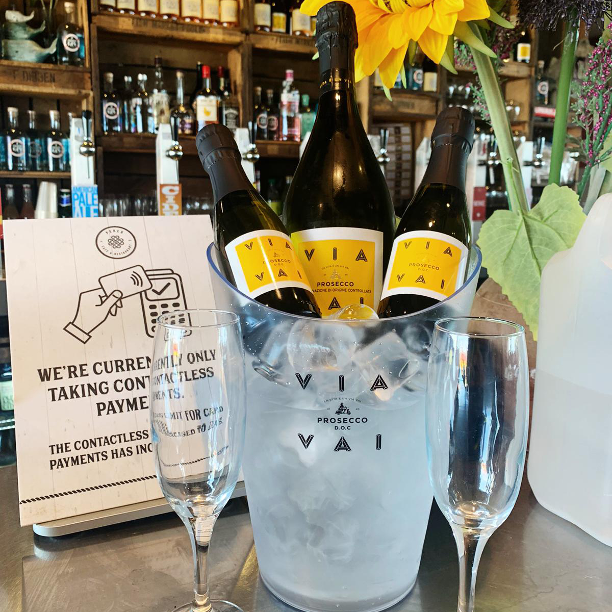 Bottles of Via Vai prosecco in a wine holder with ice and two prosecco glasses