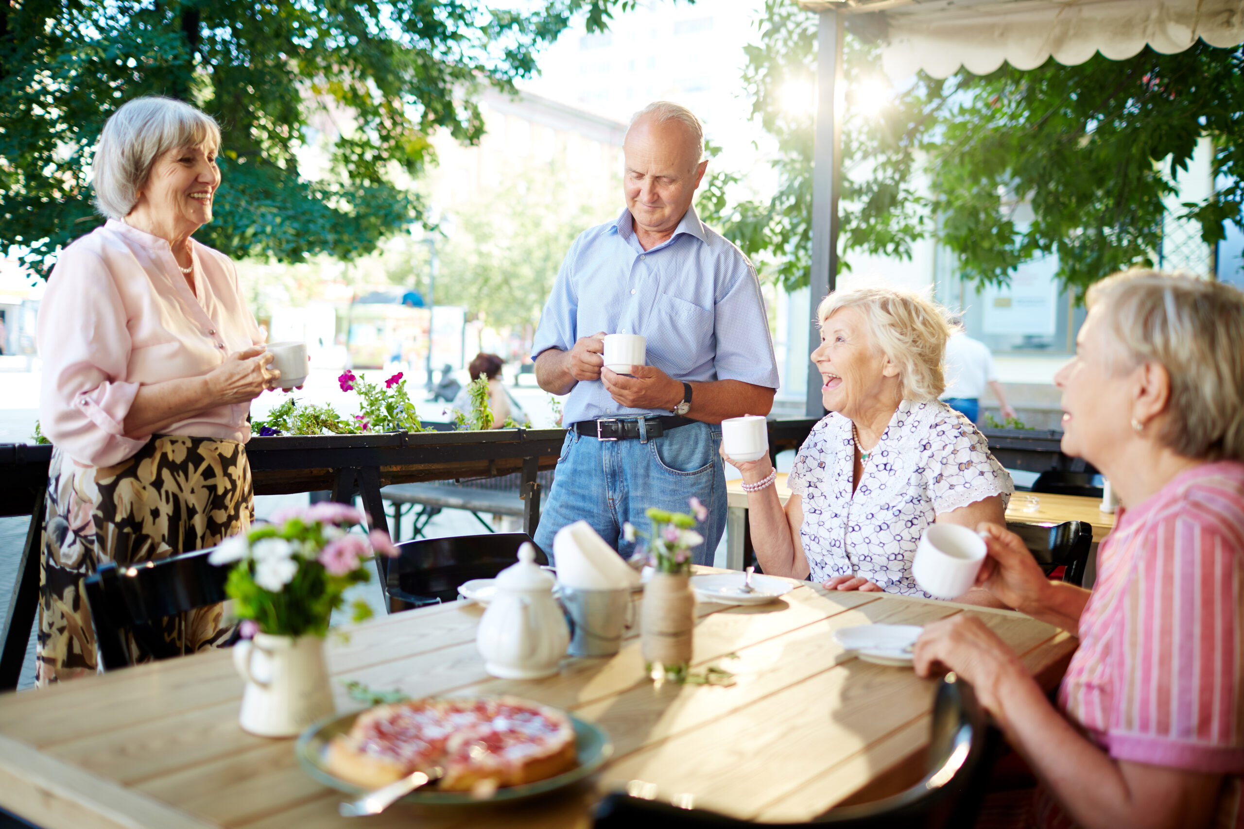 Cheerful senior friends celebrating holiday in outdoor cafe while one of them making toast; teapot and tasty pie standing on wooden table