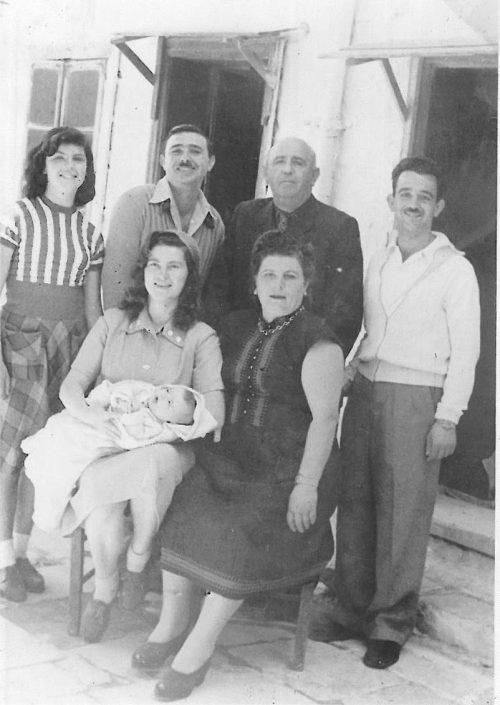 יושבות - יהודית עבו עברון ובתה התינוקת אלומה, לורה עבו, עומדים מימין לשמאל - צבי, רפאל, יוסי ועצמונה עבו