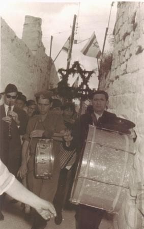 להקת הכליזמר המסורתית של סגל (השלישי משמאל) והתוף הענק שהרעיד את צפת מהקצה אל הקצה, בראש התהלוכה של ספר התורה ביציאה מבית עבו בשנות החמישים