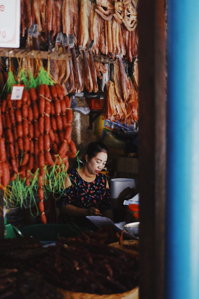 Lady selling sausages at a stall in the old market of Siem Reap Photo by Taylor Simpson on Unsplash