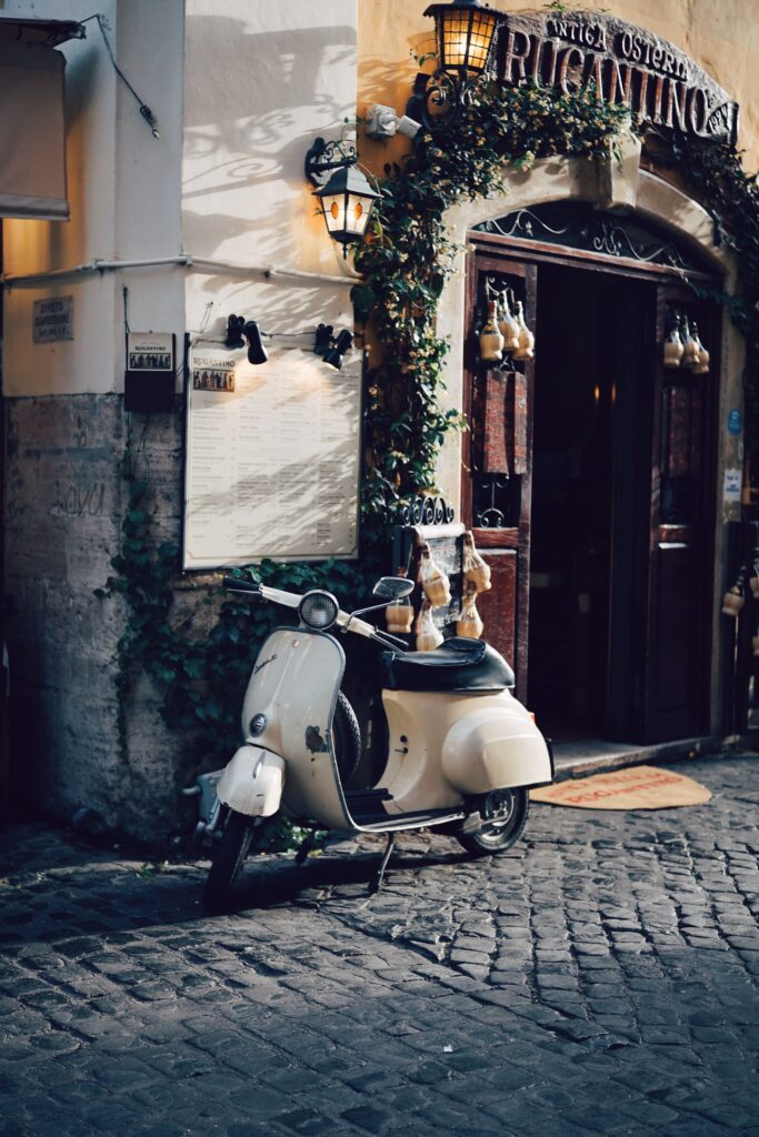 Picture of a local restaurant in the Trastevere area of Rome with a vespa outside. It is an evening view.