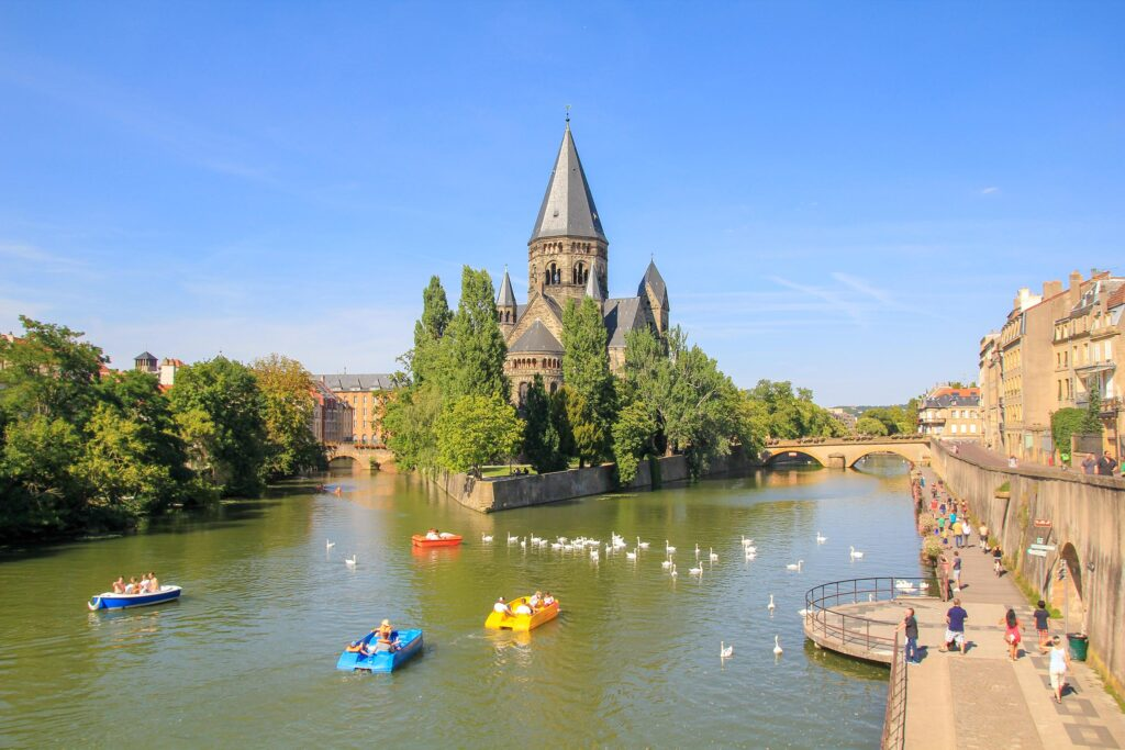 Beautiful view of Metz, hidden gems in France off-the-beaten path with a tower and boats in the river