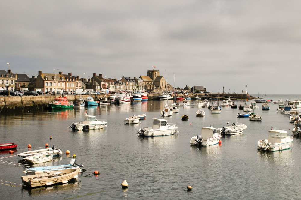 Seaside town of Barfleur, a hidden gems in France off-the-beaten path with a view of the sea with various boats anchored.