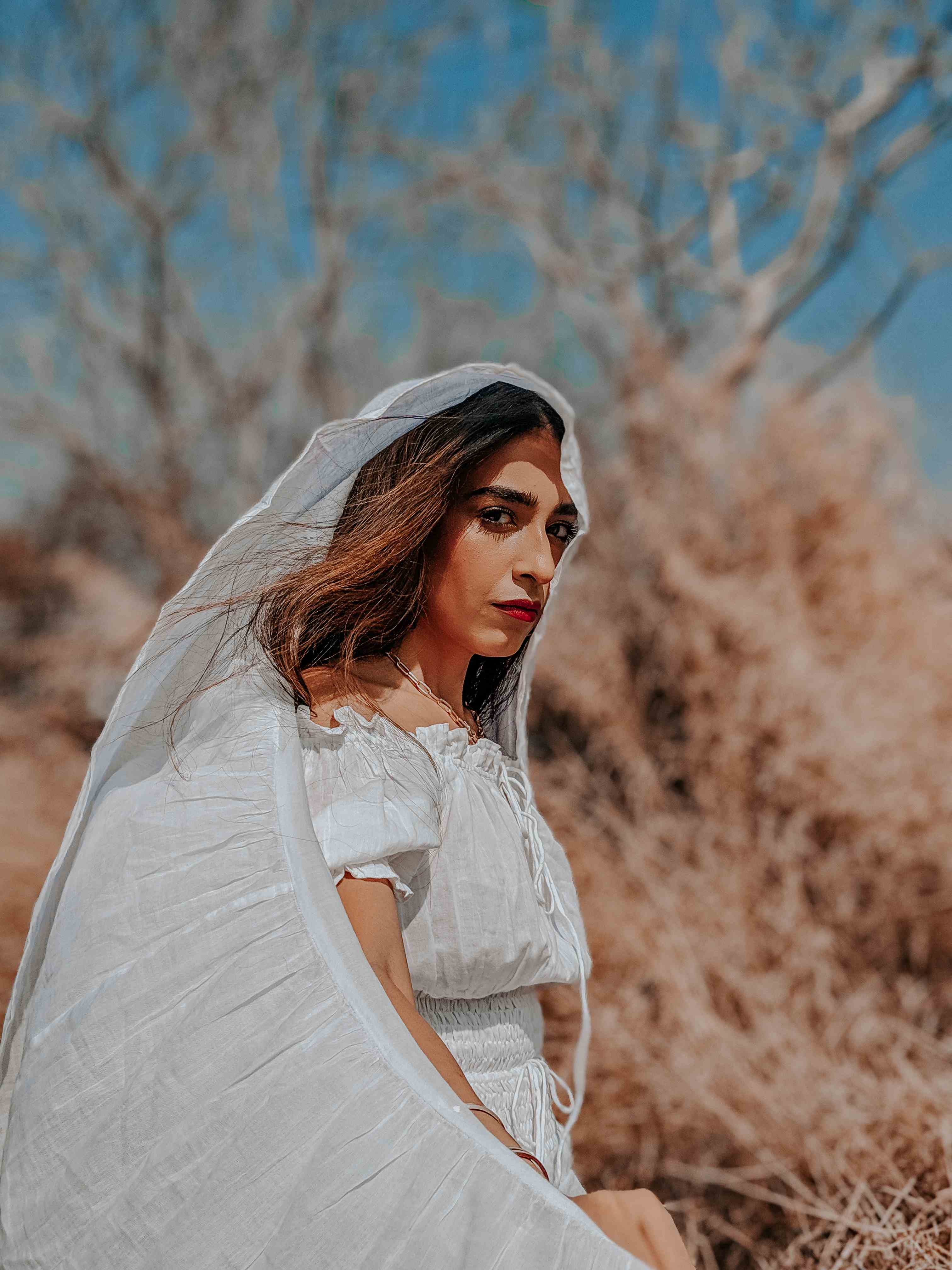 Outdoor editorial fashion shoot with girl in white dress & veil