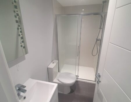 White and silver bathroom with stone tile flooring installed by Top Drawer Construction Woking Weybridge Surrey