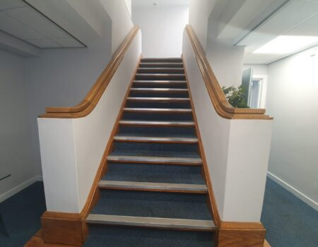 Carpeted staircase fitting with white decor and wooden trim installed in an apartment hallway lobby by Top Drawer Construction Woking Surrey