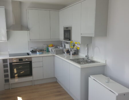 Top Drawer Construction white and chrome kitchen fitted in studio apartment Woking Surrey