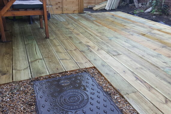 Top Drawer Construction garden decking installation with manhole cover Woking Weybridge Surrey