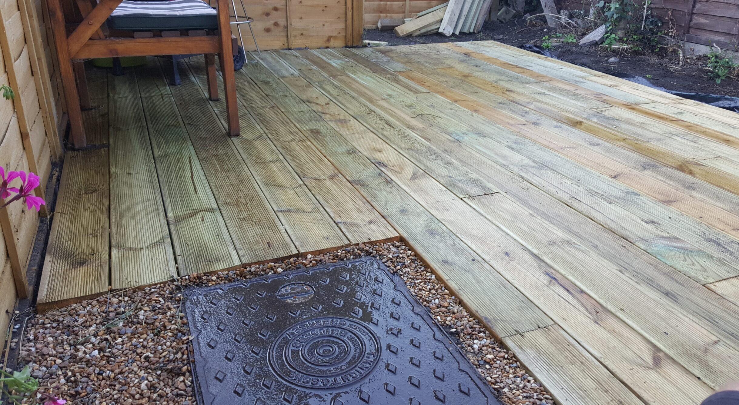 Top Drawer Construction garden decking installation with manhole cover Woking Weybridge Surrey