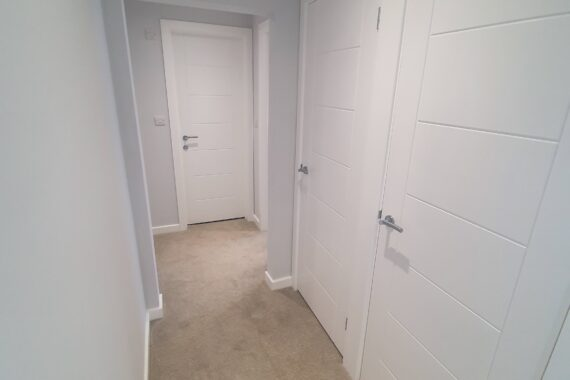 Top Drawer Construction bespoke carpentry white doors fitted in an apartment hallway Woking Weybridge Surrey