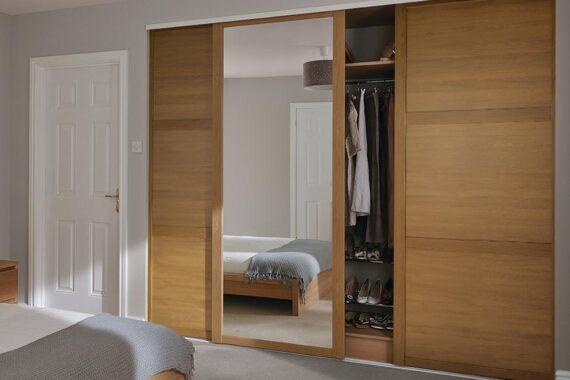 Built in bedroom wardrobes with wooden and mirrored sliding door installed by Top Drawer Construction Woking Weybridge Surrey