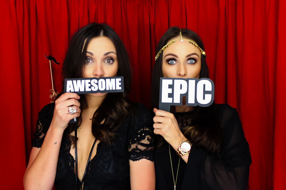 beautiful ladies in a black and red photo booth using awesome and epic word props