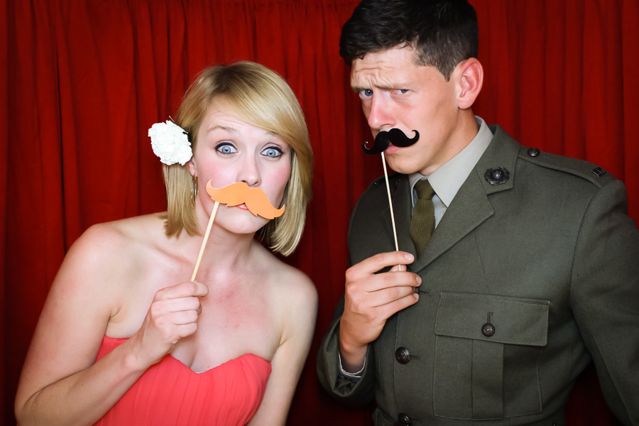posing with moustaches in the wedding photo booth