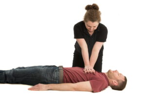 Trainer demonstrating hand placement for CPR on a casualty