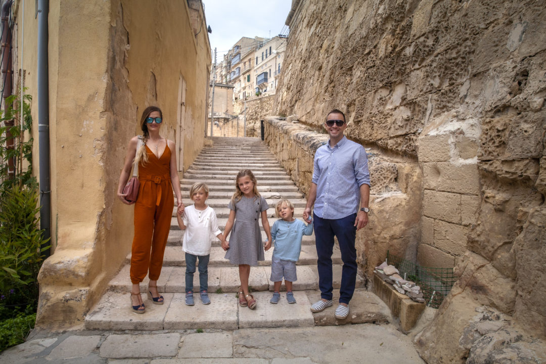 family standing holding hands in stone alley way