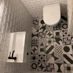 Patterned black and white floor with metro cloakroom tiles. Cloakroom basin with black tap and wall hung toilet